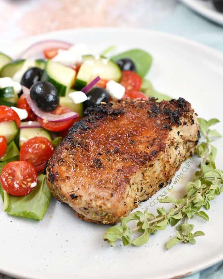 Boneless, Greek Pork Chops served with a Greek salad and sprigs of fresh oregano