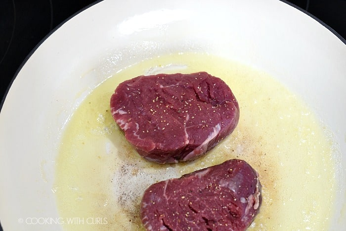 Two steaks in a skillet with melted butter and oil