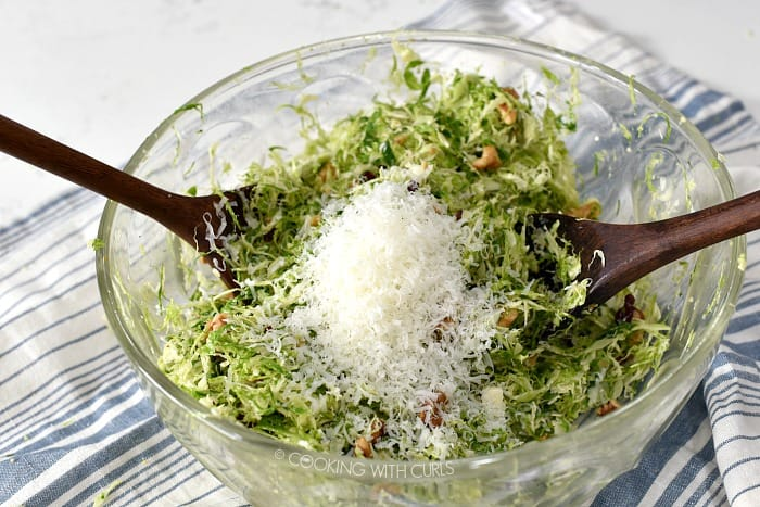 A pile of Pecorino Romano on top of shaved brussels sprouts in a large glass bowl.