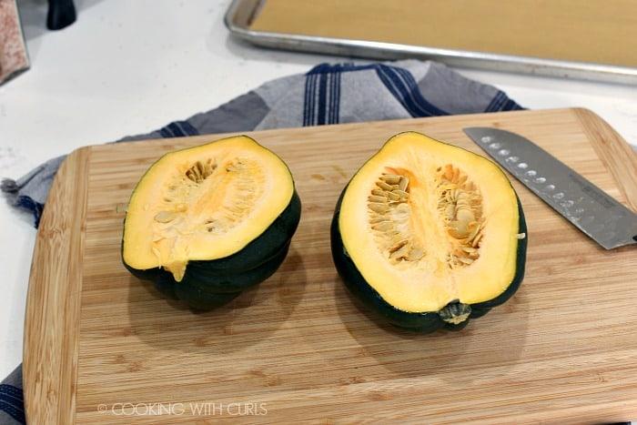 An acorn squash cut in half on a wood cutting board