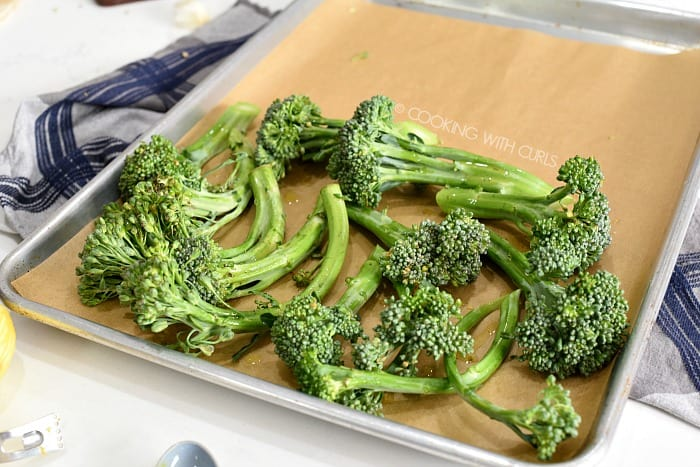 Broccolini placed on half of a parchment paper lined baking sheet