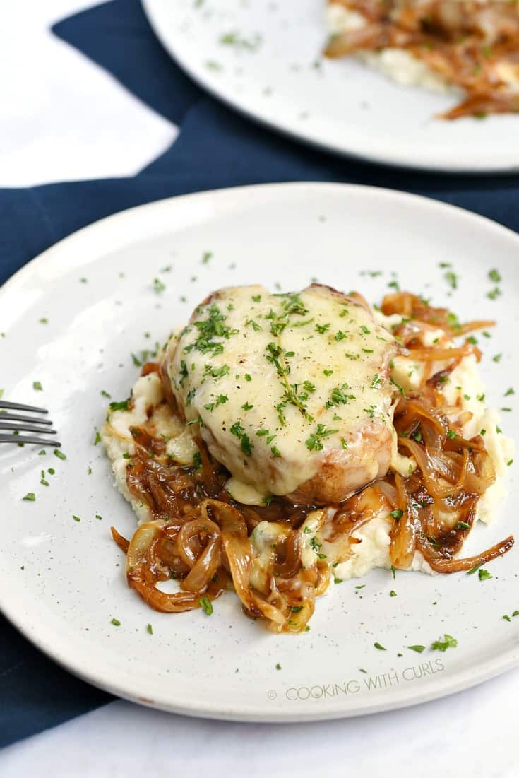 A pork chops smothered in melted cheese sitting on a bed of mashed cauliflower and caramelized onions.