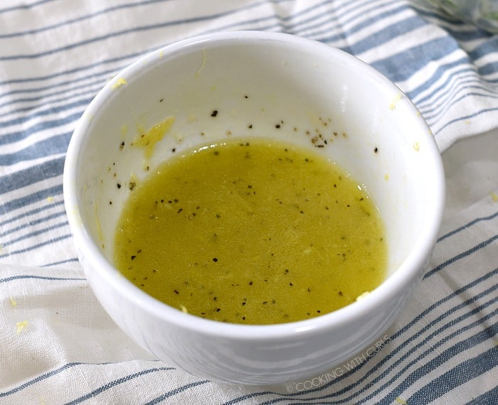 Lemon vinaigrette in a small white bowl sitting on a blue and white striped towel