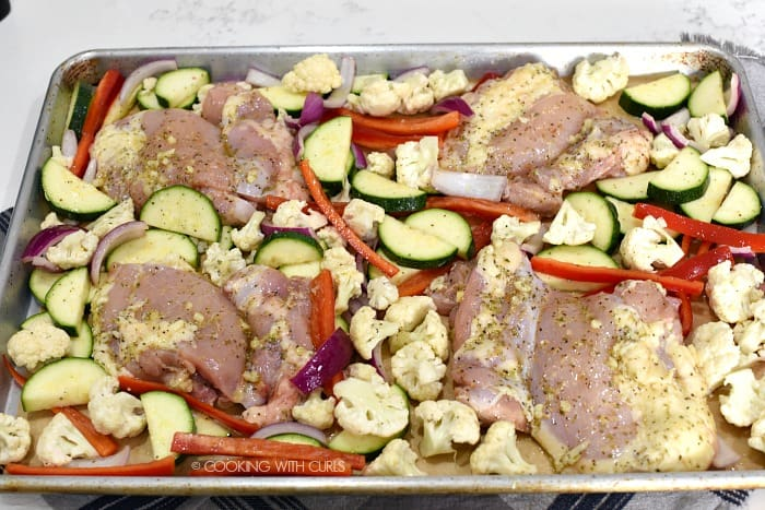 Marinated chicken added to the vegetables on the sheet pan