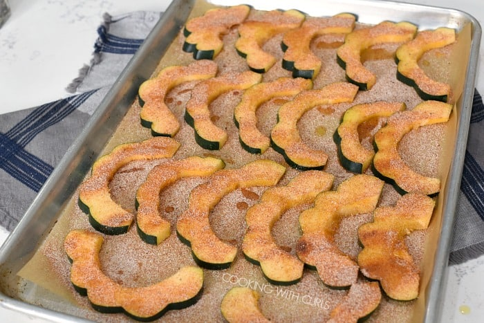 Seasoned acorn squash slices on a parchment lined baking sheet
