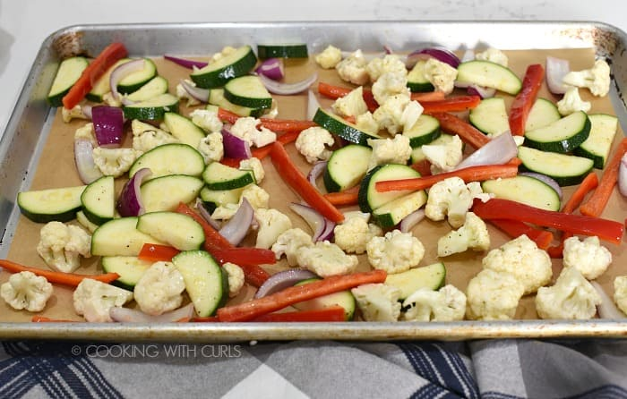 Seasoned vegetables on a parchment lined baking sheet