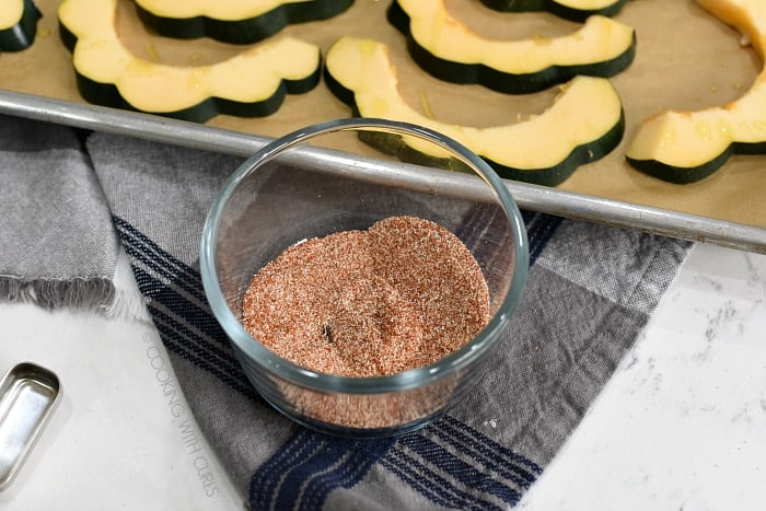 Seasoning mixture in a small glass bowl with the sliced acorn on a baking sheet in the background