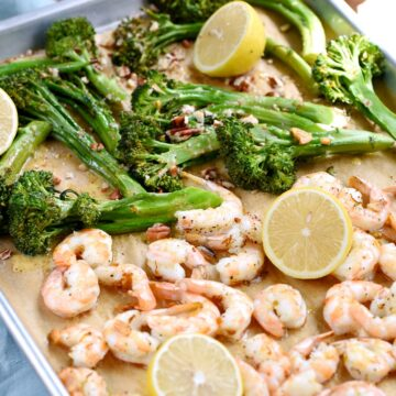 Shrimp, broccolini and lemons on a parchment paper lined sheet pan