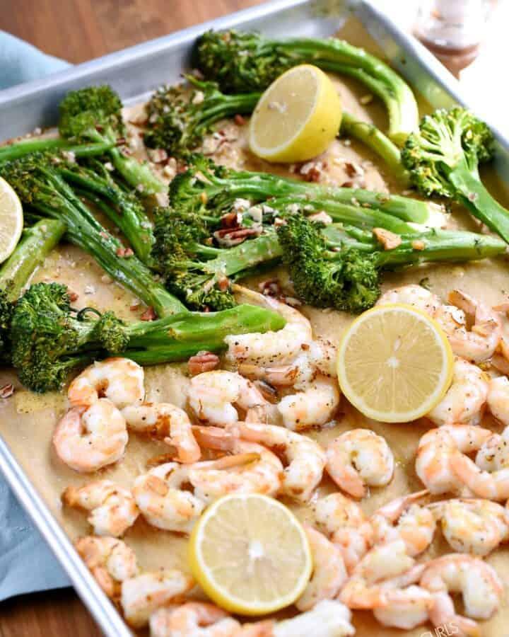 Shrimp, broccolini and lemons on a parchment paper lined sheet pan