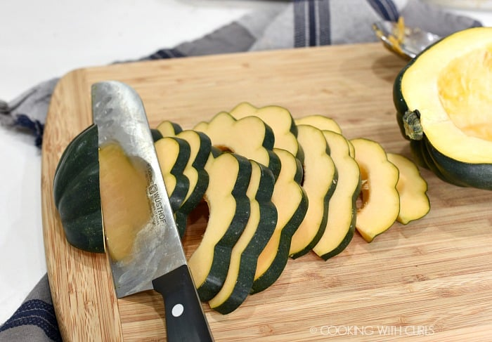 Sliced acorn squash on a wood cutting board