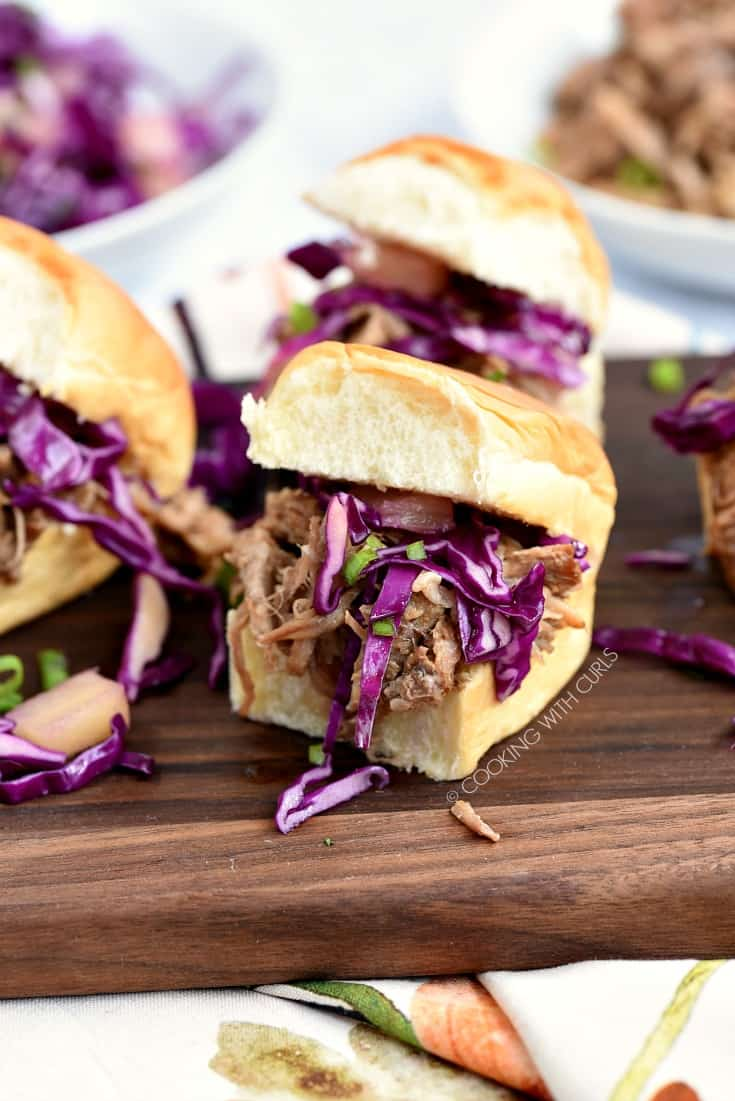 Hawaiian Pulled Pork sandwiches topped with pineapple slaw sitting on a wood board