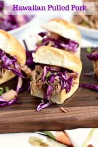 Hawaiian Pulled Pork sandwiches topped with pineapple slaw sitting on a dark wood serving board