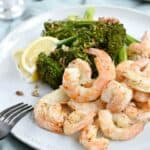 A large white plate topped with shrimp, lemon wedges and broccolini