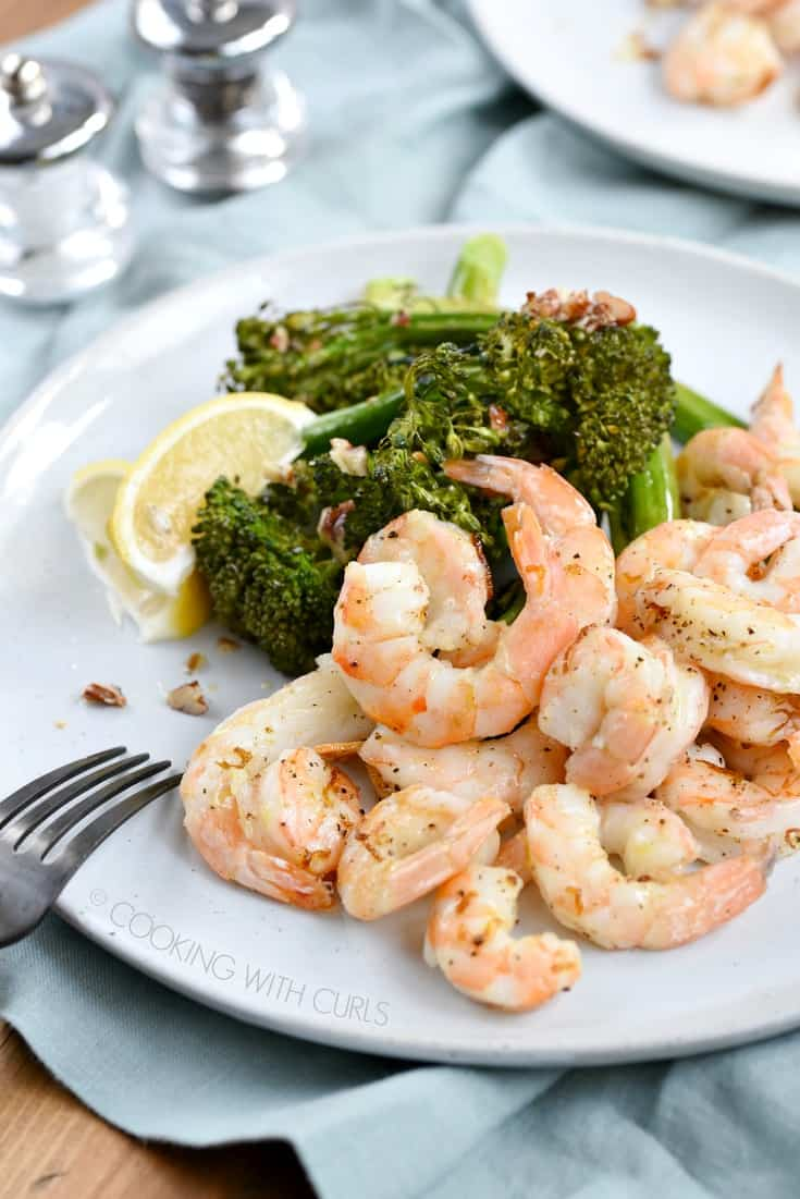 Shrimp, broccolini and lemon wedges on a large white plate