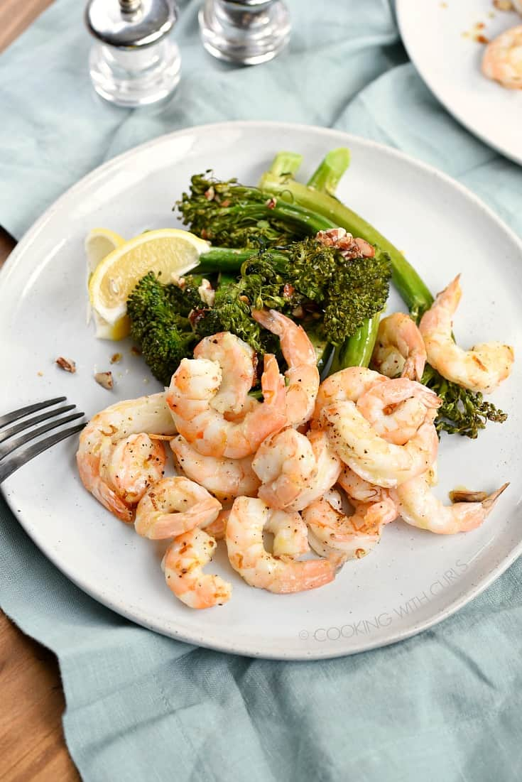 An overhead shot of shrimp, lemon wedges and broccolini on a large white plate