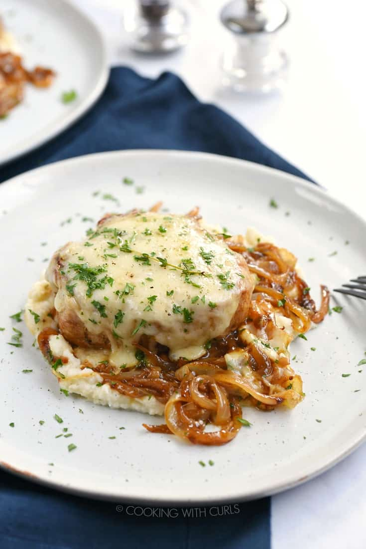 French Onion Pork Chop smothered in melted cheese and caramelized onions on a white plate