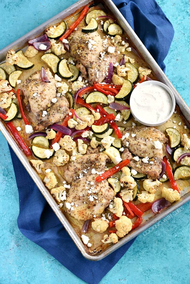 Overhead image of roasted chicken and vegetables on a parchment lined sheet pan