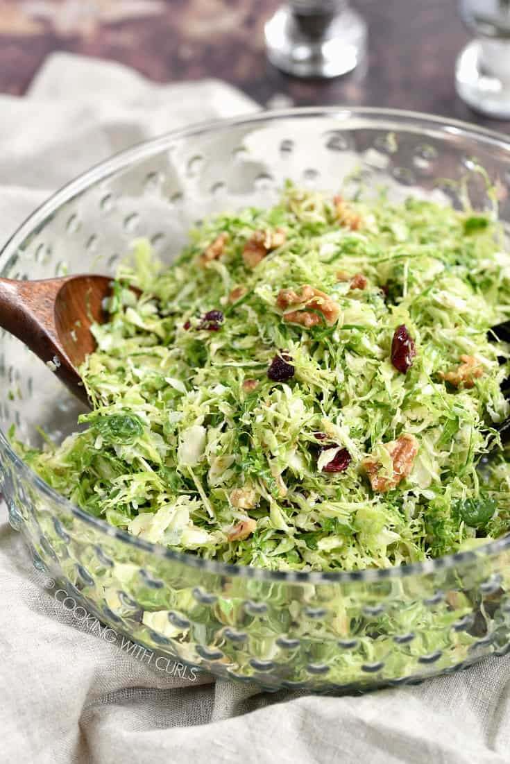A clear glass serving bowl of Shaved Brussels Sprouts Salad with two wooden spoons for serving.