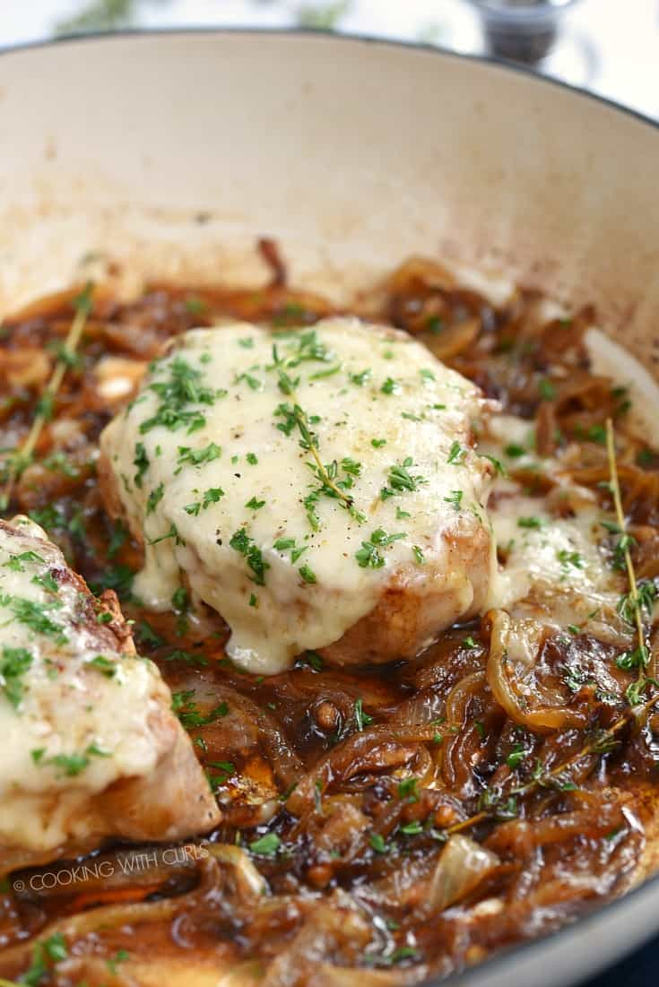 Caramelized onion and cheese covered pork chops in a cast iron skillet
