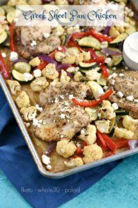 Chicken and vegetables on a sheet pan, topped with feta cheese