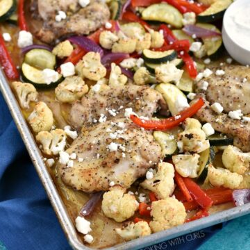 Chicken and vegetables on a parchment lined sheet pan topped with feta cheese