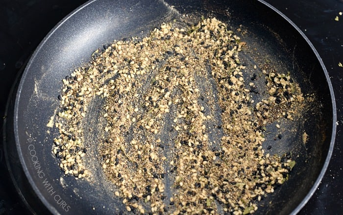 A small skillet with spices and sesame seeds