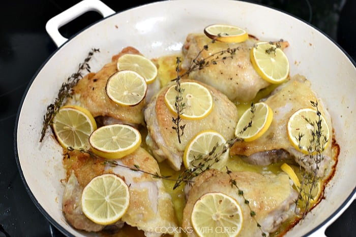 Baked chicken thighs, lemon slices and thyme sprigs