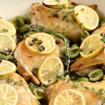 Close up image of chicken thighs topped with olives, capers, lemon slices and thyme