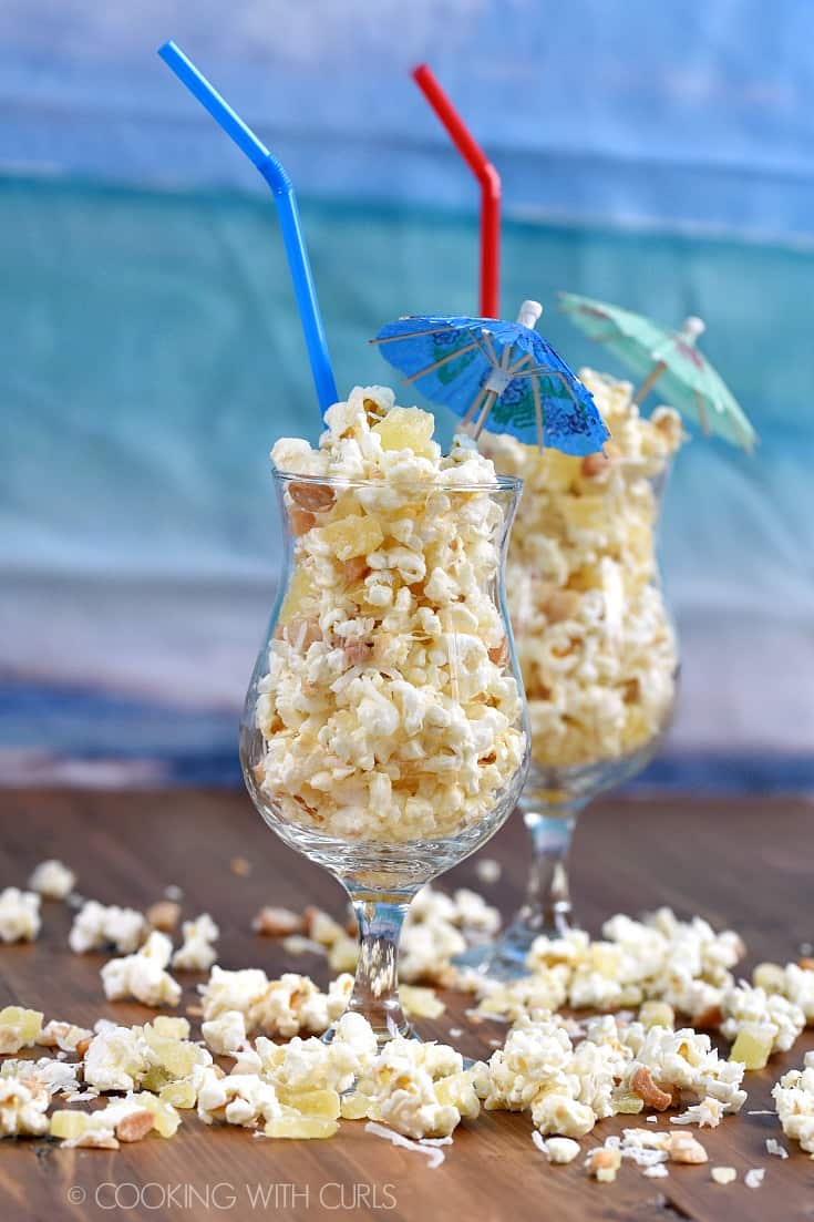 Two cocktail glasses filled with Pina Colada Popcorn with straws and paper umbrellas