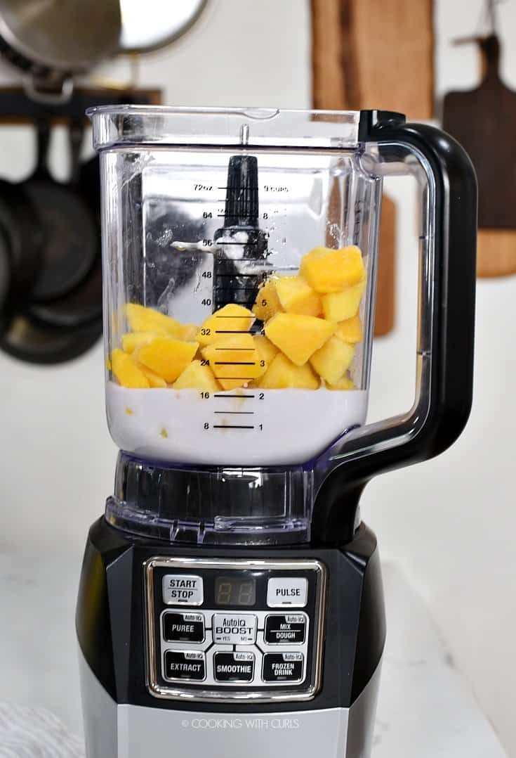 Frozen pineapple and mango chunks with coconut milk in a blender