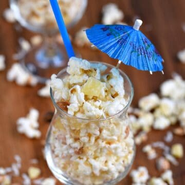 Pina Colada Popcorn in a cocktail glass with a straw and paper umbrella stick out of the top of the glass and popcorn scattered around the table
