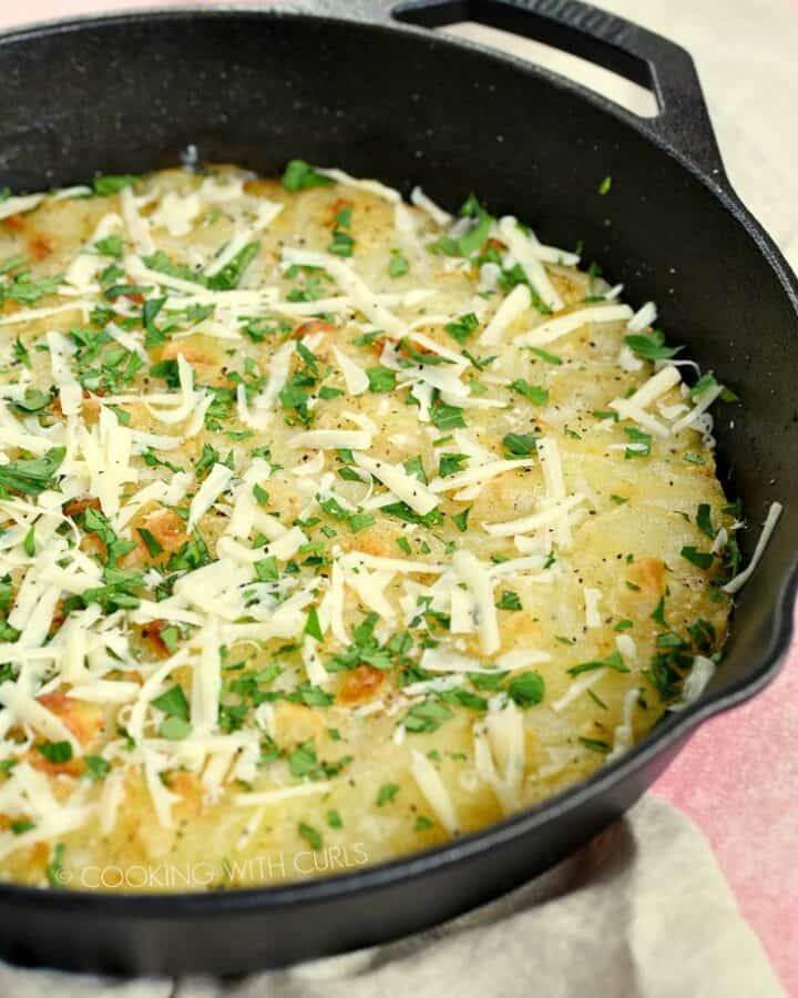 Sliced potatoes baked in a cast iron skillet topped with cheese and parsley