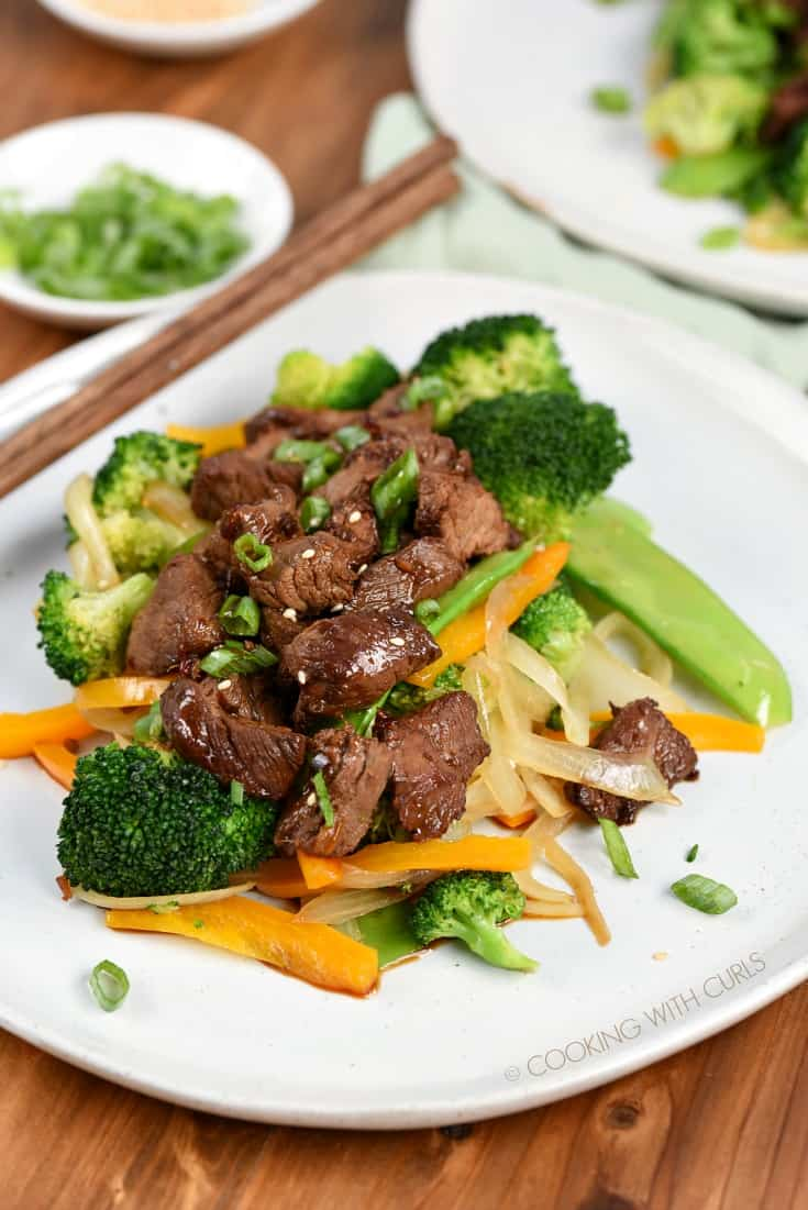 Korean BBQ Steak Tips served over stir-fry vegetables and garnished with sesame seeds and green onions
