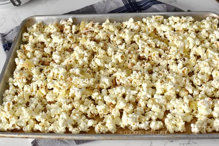 Pina Colada Popcorn spread out over a parchment lined baking sheet