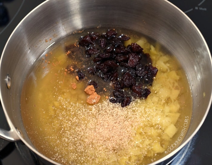 Pineapple, water, cherries, cinnamon and nutmeg in a saucepan