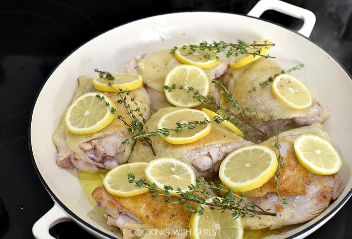 Seared chicken thighs topped with lemon slices and thyme sprigs in a large white skillet