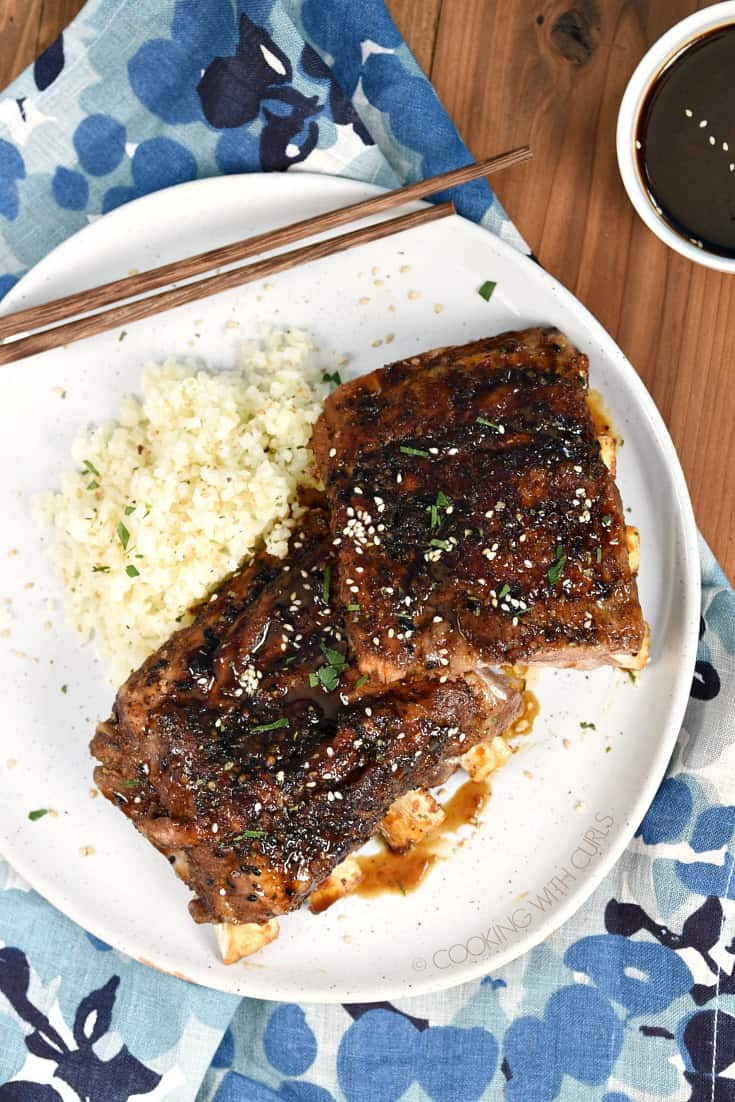 Looking down on Instant Pot Teriyaki Ribs on a white plate with cauliflower rice and a small bowl of teriyaki sauce in the upper right hand corner