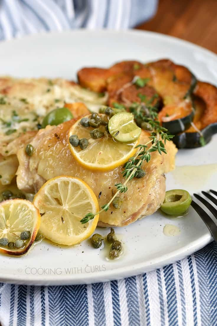 Chicken thigh topped with lemon slices, olives and capers surrounded by squash and pommes anna on a white plate