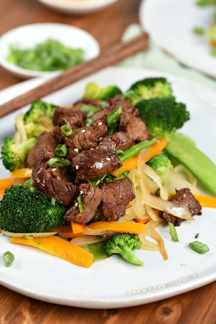 Marinated Korean BBQ Steak Tips garnished with sesame seeds and green onion slices served over stir-fry vegetables