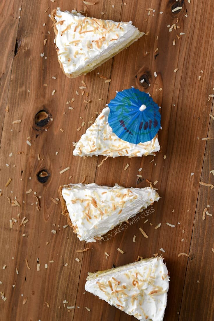 Overhead view of four slices of Pina Colada Pie, one slice with a blue cocktail umbrella