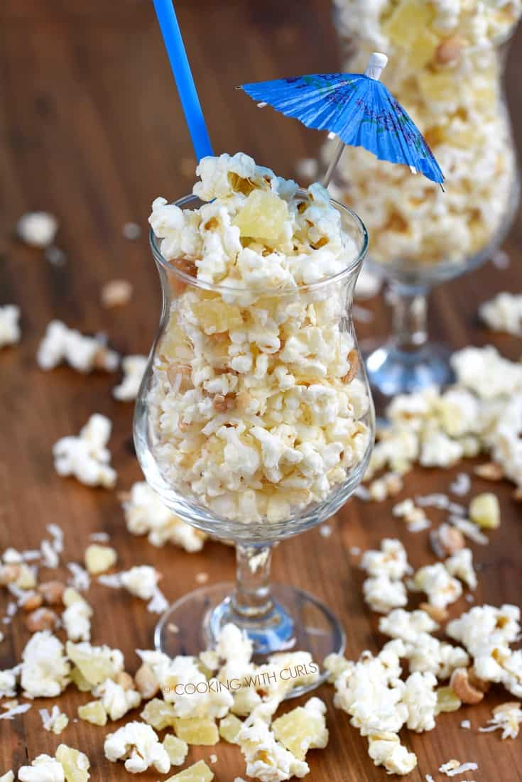 Pina Colada Popcorn overflowing a cocktail glass with a straw and paper umbrella sticking out the top of the glass
