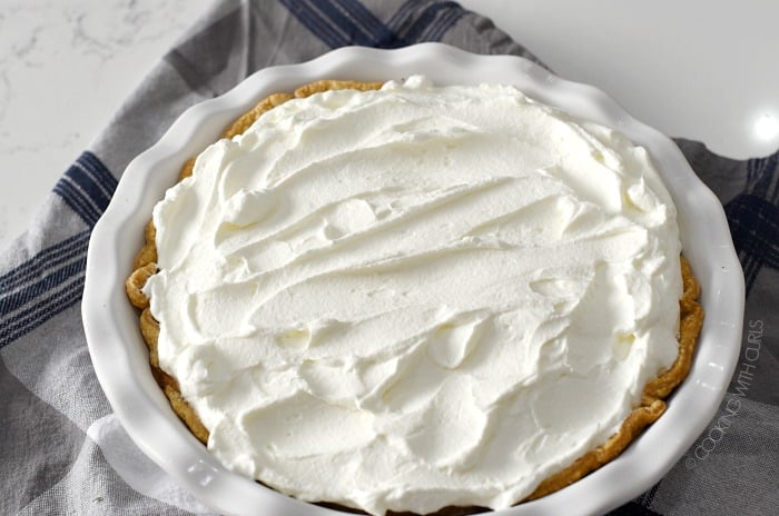Whipped cream spread over the top of the pie