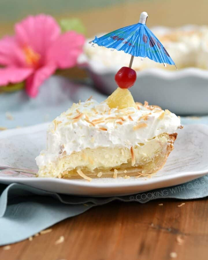 A slice of Pina Colada Pie on a wavy plate topped with a cherry and blue cocktail umbrella