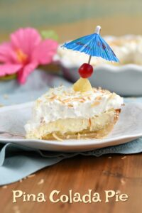 Side view looking at a slice of PIna Colada cream Pie topped with a cherry and blue cocktail umbrella