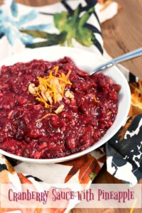 Cranberry Sauce with Pineapples in a white bowl and garnished with orange zest and chopped walnuts