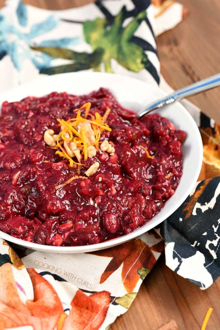 Cranberry Sauce with Pineapple in a white bowl garnished with orange zest and chopped walnuts