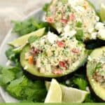Three Healthy Tuna Stuffed Avocado on a bed of cilantro leaves