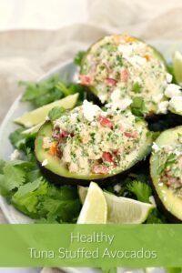 Three Healthy Tuna Stuffed Avocado on a bed of cilantro leaves