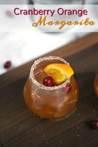 A glass filled with Cranberry Orange Margarita garnished with an orange wedge and cranberries with graphic