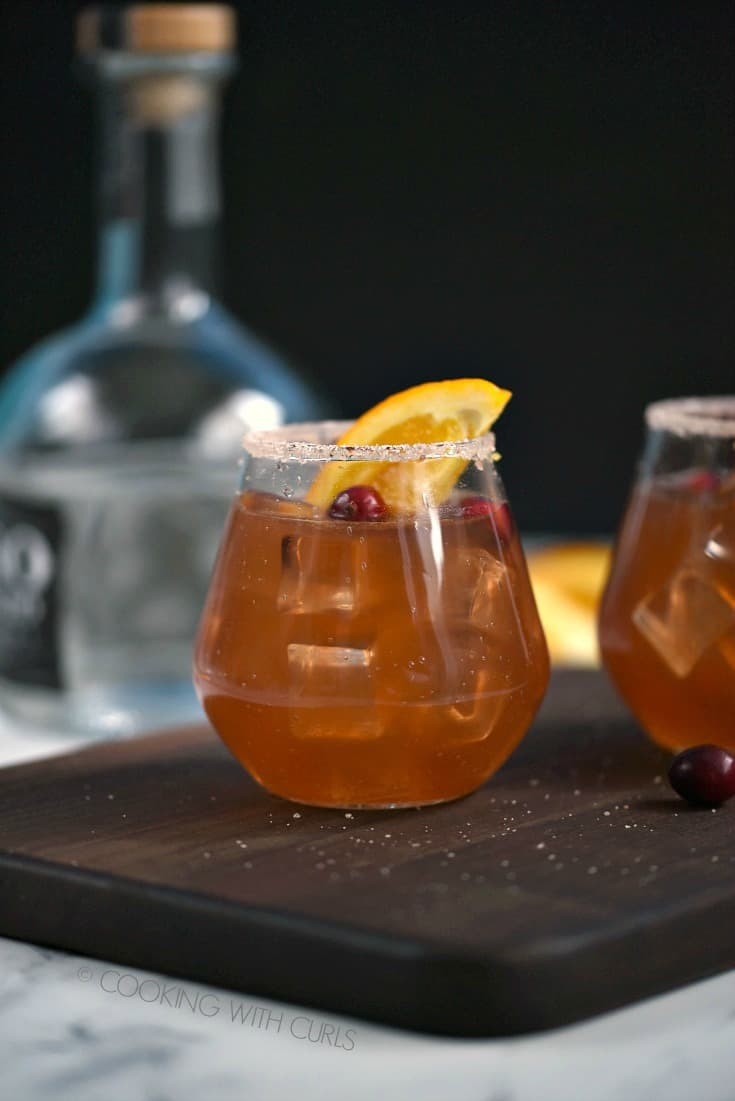 Side view of two glasses filled with Cranberry Orange Margarita garnished with an orange wedge and cranberries with a bottle of tequila in the background